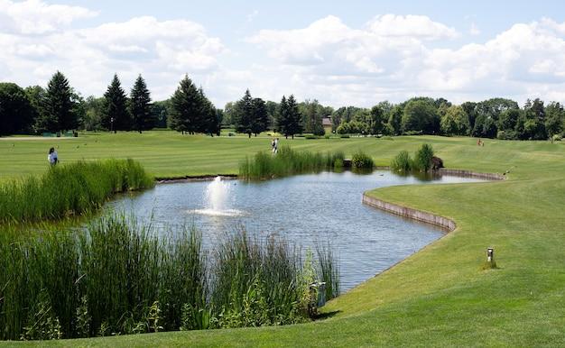 Wunderschöner golfclub mit teich und perfektem grünen rasen und gras
