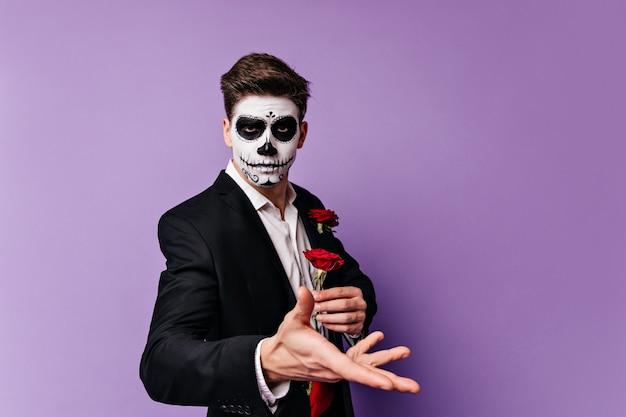 Wunderschöner junger mann mit gesichtskunst in form des schädels, der rote rose in seinen händen hält und für porträt auf lokalisiertem hintergrund aufwirft.