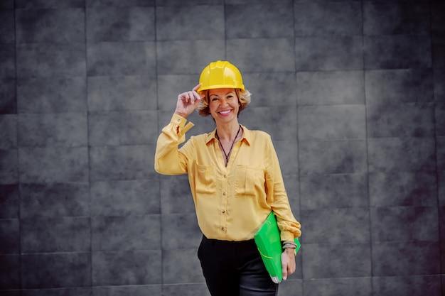 Wunderschöner kaukasischer lächelnder älterer weiblicher architekt mit helm auf kopf und dokumente unter achselhöhle, die vor grauer wand im freien aufwirft.
