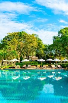 Wunderschöner luxusschirm und stuhl rund um den außenpool im hotel und resort