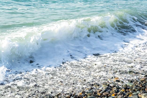 Wunderschöner meerblick mit wellen und spritzern an der strandküste an einem sonnigen tag