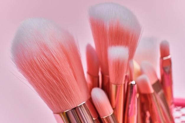 Wunderschöner satz professioneller flauschiger rosa make-up-pinsel auf einer rosa oberfläche