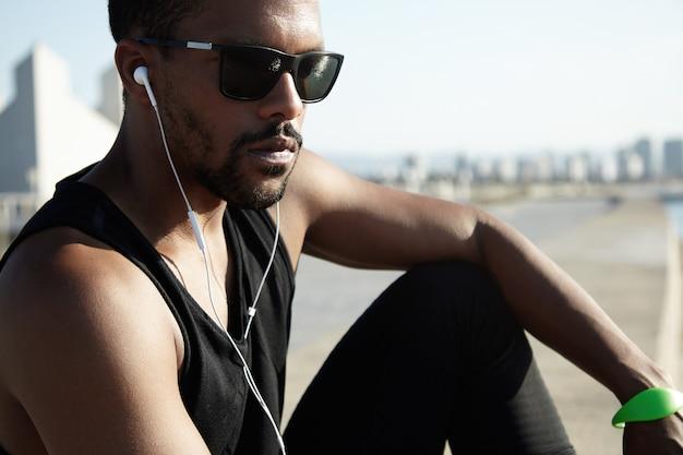 Wunderschöner schuss eines schönen dunkelhäutigen mannes in schwarzer kleidung und stilvoller sonnenbrille. hübscher mann, der nachdenklich und traurig aussieht, allein mit musik sitzend. einsame und nachdenkliche stimmung in der stadtlandschaft.