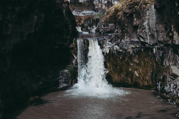 Wunderschöner schuss von wasser, das in einen teich mitten in klippen fließt