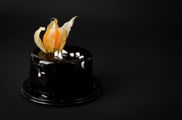 Wunderschöner schwarzer schokoladenkuchen mit schwarzem samtglasur, verziert mit physalis