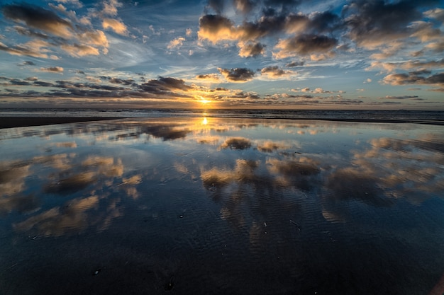 Wunderschöner sonnenaufgang, der sich im meer spiegelt und die perfekte kulisse für morgendliche spaziergänge schafft