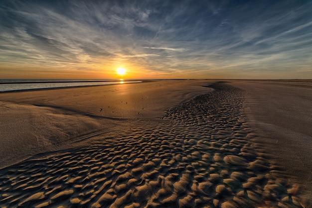 Wunderschöner sonnenuntergang am strand, der die perfekte kulisse für abendliche spaziergänge am ufer schafft