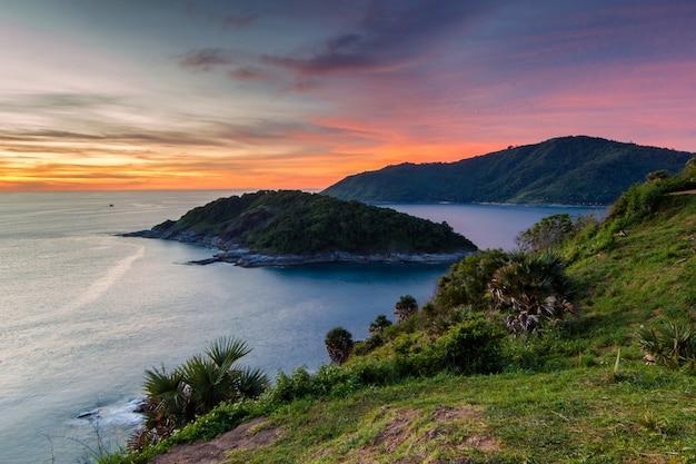 Wunderschöner sonnenuntergang in promthep cape ist ein berg aus felsen, der sich in phuket ins meer erstreckt