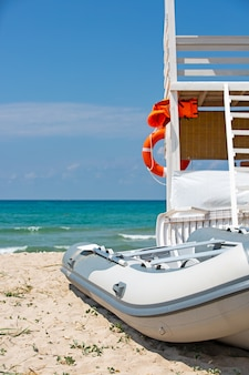 Wunderschöner tropischer strand an einem sonnigen sommertag mit einem rettungsschwimmerplatz und einem am meer geparkten boot