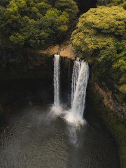 Wunderschöner wasserfall, der in den fluss fließt, umgeben von grün