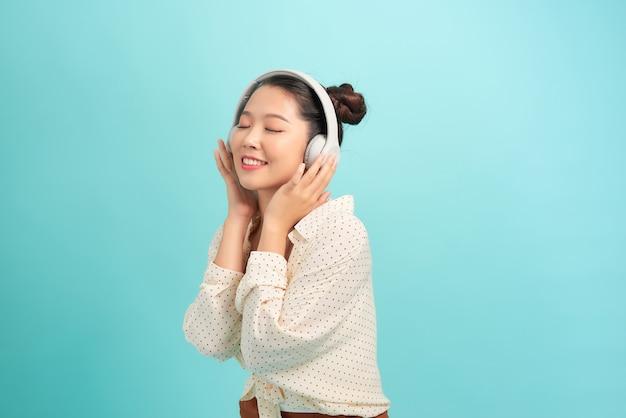 Wunderschönes asiatisches mädchen, das musik in kopfhörern hört