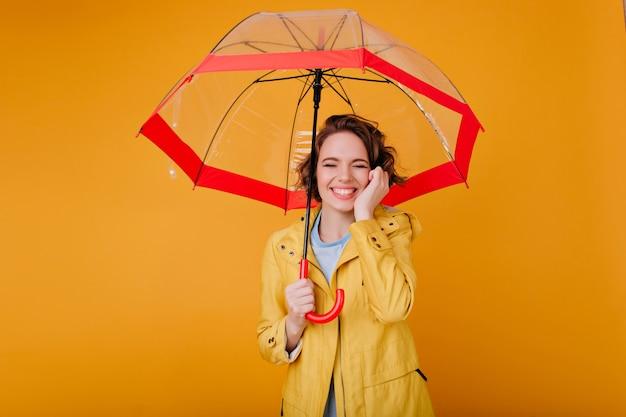 Wunderschönes blasses mädchen im herbstmantel lächelnd mit geschlossenen augen unter sonnenschirm. studioporträt der stilvollen kaukasischen frau mit dem gewellten haar, das roten regenschirm hält.