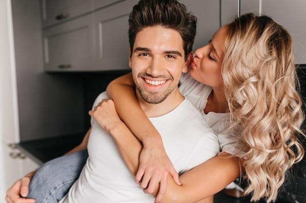 Wunderschönes blondes mädchen, das freund ins ohr küsst. innenporträt des romantischen kaukasischen paares.