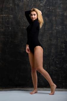 Wunderschönes blondes modell mit perfekter figur in einem schwarzen body