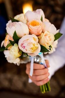 Wunderschönes bouquet mit zarten blüten. hochzeitsblumen. brautstrauß in männlichen händen