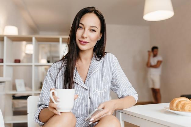 Wunderschönes brünettes weibliches modell im blauen hemd, das in der küche mit tasse kaffee aufwirft
