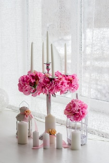 Wunderschönes dekor aus kerzen und blumen. weiße rosatöne.