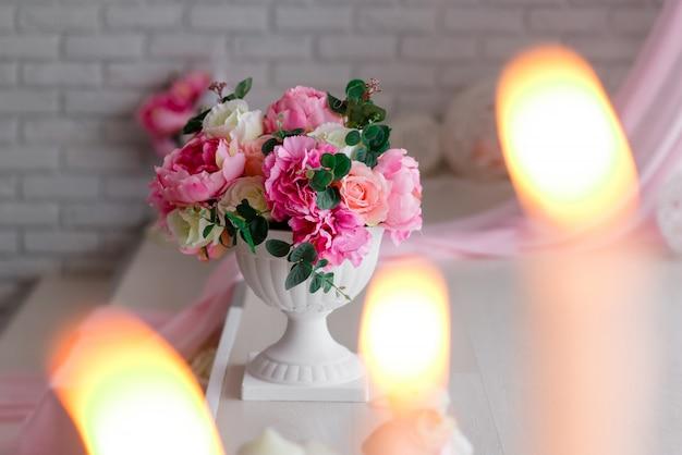 Wunderschönes dekor in weiß und pink. pfingstrosen und brennende kerzen auf hellem hintergrund.