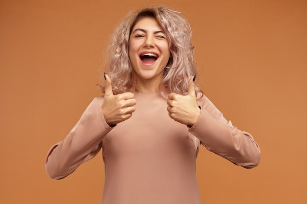Wunderschönes ekstatisches junges mädchen mit rosa haaren und nasenring, das vor aufregung schreit und daumen hoch geste macht und positive emotionen zeigt