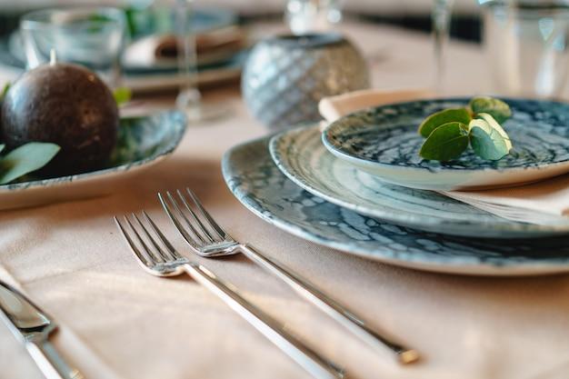 Wunderschönes elegantes gedeck mit grünem, stilvollem geschirr und silbernem besteck