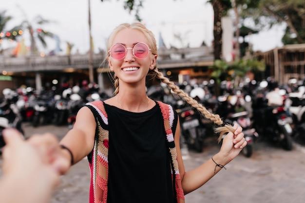 Wunderschönes europäisches weibliches modell mit zöpfen, die sommertag im freien verbringen.