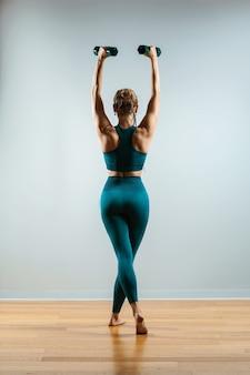 Wunderschönes fitness-modell, das übungen mit hanteln in den händen macht, die das mädchen für sport im fitnessstudio betreibt