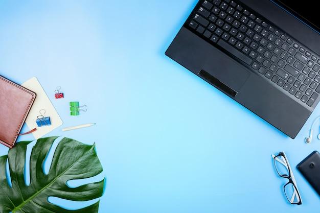 Wunderschönes flatlay mit laptop, brille, philodendronblättern und anderem geschäftszubehör. konzept eines heimbüros. flach liegen.