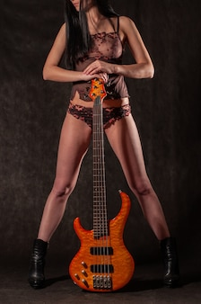 Wunderschönes high glamour model in dessous mit bassgitarre