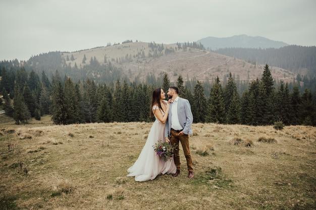 Wunderschönes hochzeitspaar, das im berg des grünen kiefernwaldes auf hintergrund umarmt.