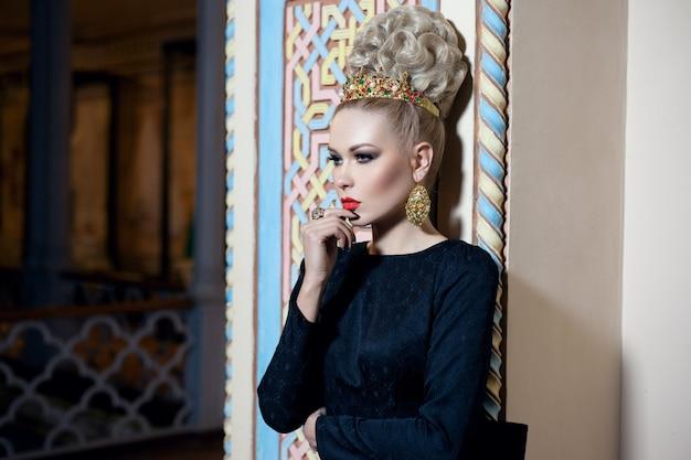Wunderschönes junges blondes weibliches model, gekleidet in ein langes schwarzes kleid mit schleife hinten, eleganter frisur und krone und ohrringen. beaty porträt.