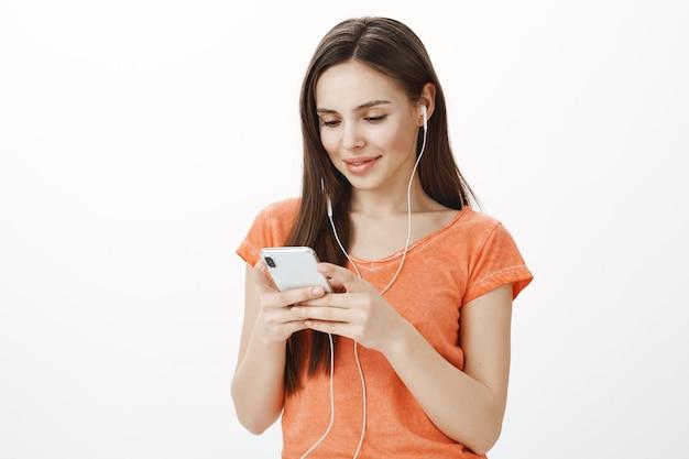 Wunderschönes junges brünettes mädchen, das musik in den kopfhörern hört und handy hält