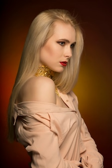 Wunderschönes junges model mit leuchtendem make-up in roter farbe und goldfolie am hals