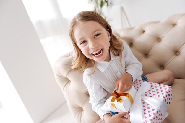 Wunderschönes kleines mädchen, das ordentlich verpackte kisten mit geschenken hält und sehr glücklich aussieht.