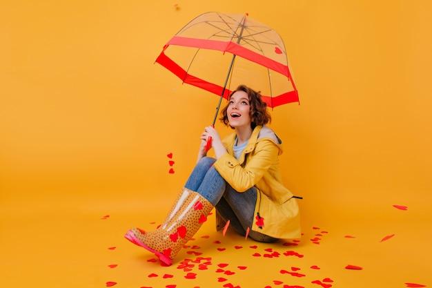 Wunderschönes kurzhaariges mädchen mit schönen augen, die unter sonnenschirm aufwerfen. innenfoto des romantischen weißen weiblichen modells, das auf gelbem boden mit regenschirm sitzt.