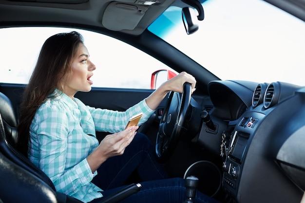 Wunderschönes mädchen, das blaues hemd trägt, das im neuen automobil sitzt, glücklich, im verkehr stecken bleibt, musik hört, porträt, handy hält, unfall.
