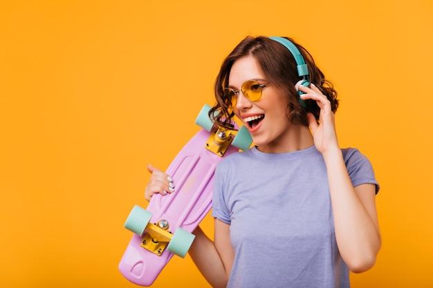 Wunderschönes mädchen in der gelben sonnenbrille, die musik in den kopfhörern hört. porträt des modischen weiblichen modells mit skateboard, das lieblingslied singt.