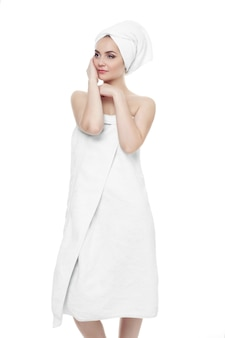 Wunderschönes mädchen mit dunklem haar und dunklen augenbrauen, das ein weißes handtuch auf dem kopf trägt und hände nahe gesicht hält. leichtes make-up. porträt der 20-25 jahre alten schönen frau, die handtuch auf ihrem kopf trägt