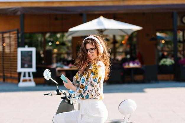 Wunderschönes mädchen mit langem lockigem haar, das hemd mit blumenmuster trägt, auf roller sitzt und handy hält