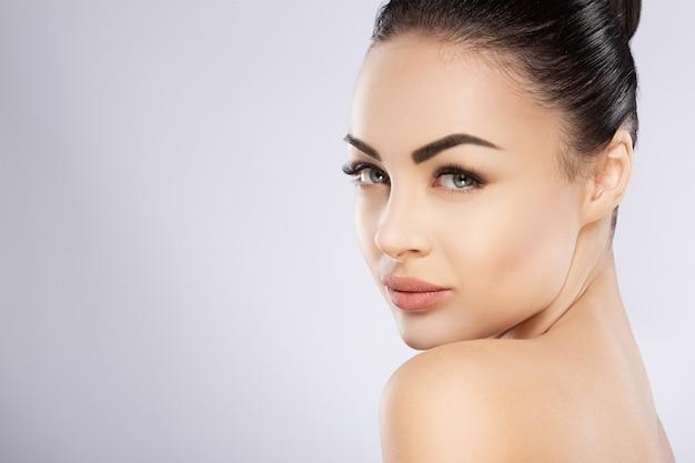 Wunderschönes mädchen mit schwarzen haaren, großen augen, dicken augenbrauen und nackten schultern in grau, ein modell mit hellem nacktem make-up, porträt.