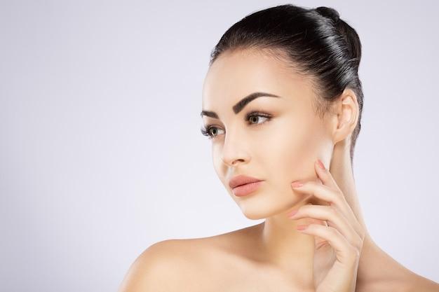 Wunderschönes mädchen mit schwarzen haaren, großen augen, dicken augenbrauen und nackten schultern in grau, ein modell mit hellem nacktem make-up