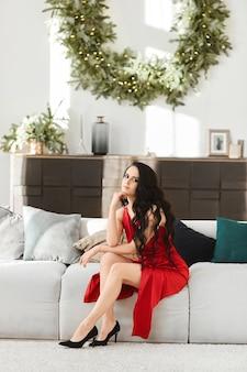 Wunderschönes model girl mit langen sexy beinen in einem roten kleid sitzt auf der couch im wohnzimmer