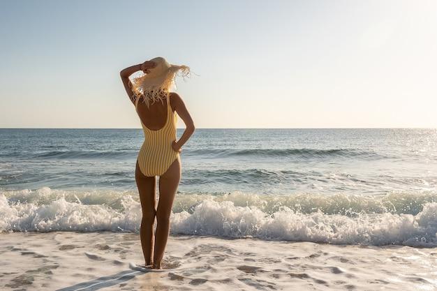Wunderschönes model im badeanzug am sandstrand