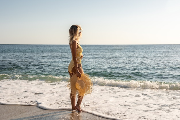 Wunderschönes model im badeanzug am sandstrand.