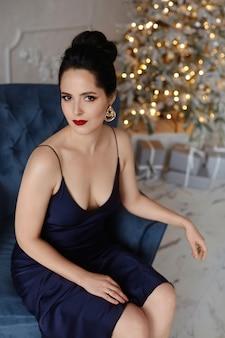 Wunderschönes model-mädchen mit hellem make-up und modischer frisur, das ein dunkelblaues abendkleid trägt, sitzt in einem vintage-sessel mit festlicher weihnachtsbeleuchtung im hintergrund