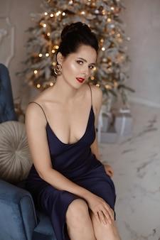 Wunderschönes model-mädchen mit langen sexy beinen, das ein dunkelblaues abendkleid trägt, sitzt in einem vintage-sessel i...