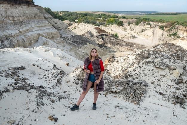 Wunderschönes model trägt einen pelzmantel, der an einem trockenen, leeren sandsteinbruch am warmen, sonnigen herbsttag steht