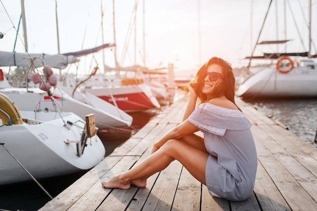 Wunderschönes modell sitzt am pier und lächelt. sie posiert. junge frau hält beine zusammen und hält haare mit der hand vom winken ab. sie sieht glücklich aus.
