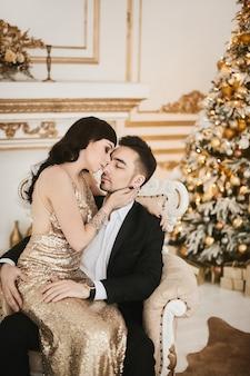 Wunderschönes modisches liebespaar auf luxuriösem interieur, das zu weihnachten dekoriert ist.
