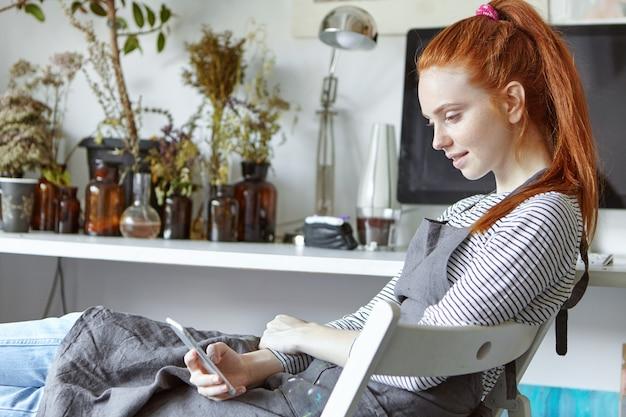 Wunderschönes rothaariges studentenmädchen, das am mal-retreat teilnimmt, neue kunsttechniken studiert, auf einem stuhl in der werkstatt sitzt und sich notizen über ihr gerät macht, nachdem es seinen gesichtsausdruck inspiriert hat