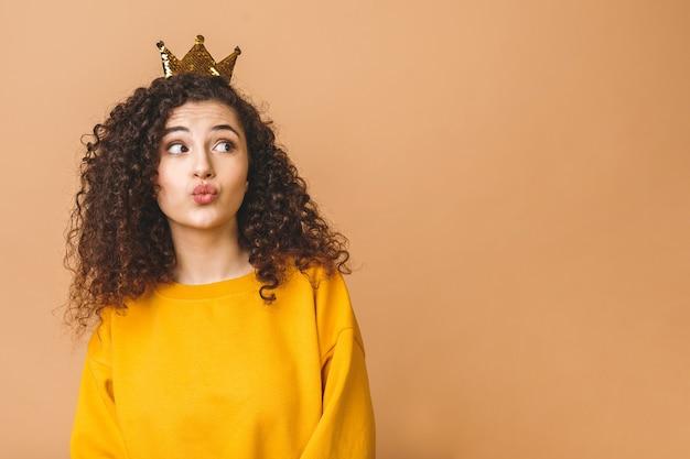Wunderschönes schönes mädchen mit lockigem braunem haar und tragen lässiger und haltender krone auf kopf lokalisiert über beigem studiohintergrund. luftkuss senden.